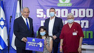 رئيس الوزراء الإسرائيلي بنيامين نتنياهو ووزير الصحة يولي إدلشتاين يلتقيان بالشخص الإسرائيلي  رقم 5 ملايين تلقى تطعيمه في إسرائيل، 8 آذار / مارس، 2021