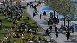 People take a break on a bank of the Rhône river in Lyon, south-eastern France, one of the new areas to have restrictions tightened,  on March 25, 2021. .