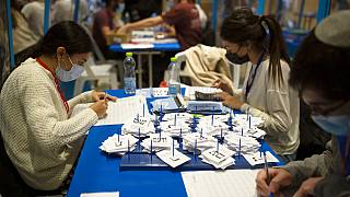 Workers count votes in Israel's national elections wearing and divided in groups by sheets of plastic masks to help curb the spread of the coronavirus, at the Knesset.