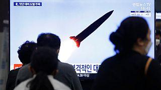 كوريون جنوبيون في محطة قطارات سوسيو في سيول يتابعون إطلاق صاروخ كوري شمالي خلال برنامج إخباري، 25 مارس 2021