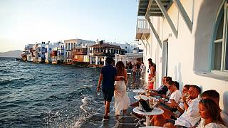 People sit at a bar in Little Venice on the Aegean Sea island of Mykonos