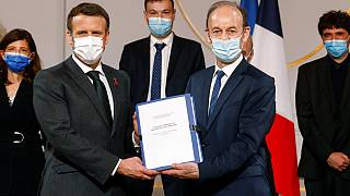 Historian Vincent Duclert, right, gives a report to French President Emmanuel Macron, at the Elysee Palace, in Paris, Friday, March 26, 2021.