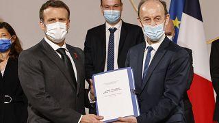 الرئيس الفرنسي إيمانويل ماكرون يحمل وثيقة مشتركة إلى جانب المؤرخ فنسنت دوكلرت، الذي يرأس اللجنة الرواندية في قصر الإليزيه