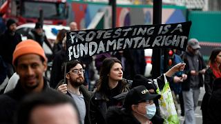 People hold signs during a protest against government restrictions to curb the spread of the coronavirus, in London, Saturday, March 20, 2021.