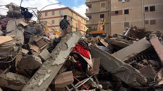 Emergency workers sift through the rubble of a collapsed apartment building in the el-Salam neighborhood