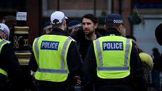 Police speak with demonstrators during a protest against government restrictions to curb the spread of the coronavirus, in London, March 20, 2021.