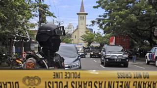 A police officer stands guard near a church where an explosion went off in Makassar, South Sulawesi, Indonesia, Sunday, March 28, 2021.