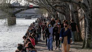 People stroll along the Seine river bank in Paris, where hospitals are under significant pressure from COVID-19 patients