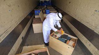 موظف في وزارة الإعلام الكويتية يتفقد صناديق أرشيفات كويتية بعد استردادها من العراق، 28 مارس 2021