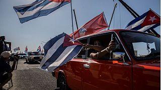 Gente con banderas cubanas en un Lada en La Habana