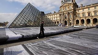 FILE: French street artist JR walks in the courtyard of the Louvre Museum near the glass pyramid designed by architect Leoh Ming Pei, in Paris, 27th March 2019