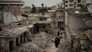 نساء يسرن في حي تضرر بشدة من الغارات الجوية في إدلب ، سوريا/ 12 مارس / آذار 2020