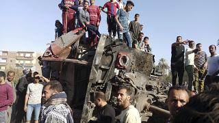 يتجمع مصريون حول عربات قطار مشوهة في موقع حادث قطار في مدينة سوهاج بجنوب مصر - 26  آذار / مارس 2021
