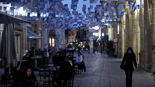 People sit and drink, outside a coffee shop, in Faneromeni square in the capital Nicosia, Cyprus