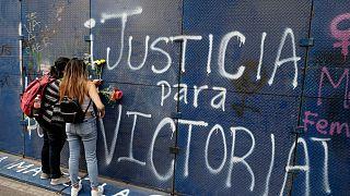 Jóvenes mexicanas colocan flores ante un grafiti que pide 'Justicia para Victoria' en Quintana Roo, México