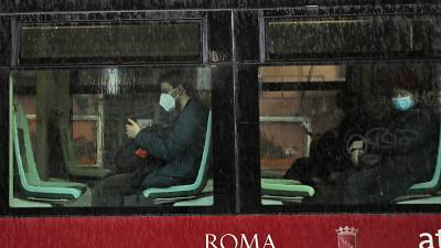 People wearing face masks to curb the spread of COVID-19, sit at distance in a tram in downtown Rome, Monday, March 15, 2021.