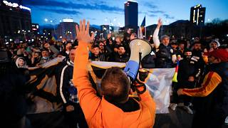 Protestors shouted slogans outside the Romanian government headquarters in Bucharest.