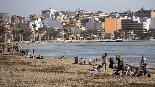 Tourists enjoy the beach at the Spanish Balearic Island of Mallorca, Spain, Monday, March 29, 2021.