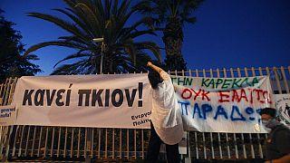 Διαδηλώτρια κρεμάει πανό που γράφει «Αρκετά»