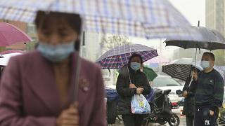 People wearing face masks to protect against COVID-19 wait in the rain to pick up children from a school in Wuhan.
