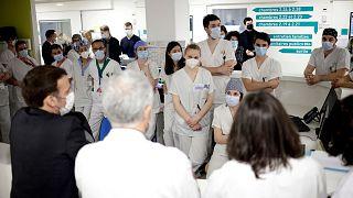 French President Emmanuel Macron speaks with staff in hospital