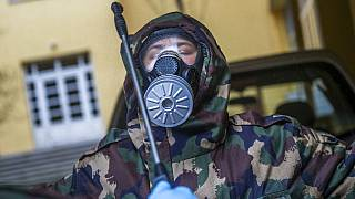 A Hungarian soldier wearing a hazmat suit clears himself after completing the disinfection of a combined kindergarten and elementary school in Budapest, Hungary