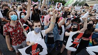 """Protesters with a banner reading """"Women's Strike"""" in a rally against Polish government"""