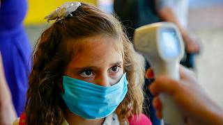 A pupil wearing a face mask to protect against coronavirus, has her temperature checked in the capital Pristina, Kosovo, Monday, Sept. 14, 2020.