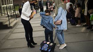 A child and his mother are welcomed by the director of the primary school during the first day of classes in Brussels.