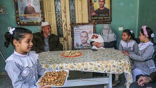 إيمان زوجة الأسير الفلسطيني محمد القدرة تحمل طفلها المولود حديثًا من حيوانات منوية مهربة مع والد زوجها وبناتها الثلاث في مخيم للاجئين في خان يونس جنوب غزة