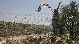 İsrail'in dikenli tellerle çevirdiği Naalin köyünde elinde Filistin bayrağı ile protesto yapan bir eylemci (arşiv)