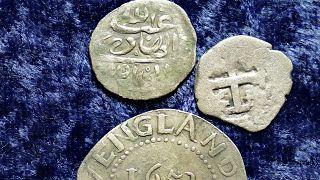 Egy 1693-ban Jemenben vert érme, egy 1652-es Oak Tree Shilling Massachusettsből és egy spanyol félreálos érme
