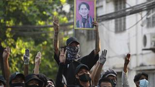 Anti-coup demonstrators raise the three finger of resistance and a portrait of deposed leader Aung San Suu Kyi. Yangon, Myanmar. April 1, 2021.