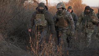 Ukrainian President Volodymyr Zelenskiy, left, inspects Ukrainian armed forces' positions as he visits Donetsk region, Ukraine, Sunday, Dec. 6, 2020