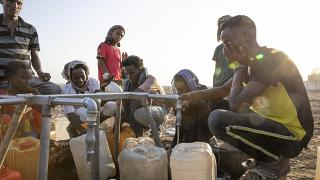 Tigrayan refugees fill their gallons with water at a water station at Hamdeyat Transition Center near the Sudan-Ethiopia border, eastern Sudan, March 24, 2021.