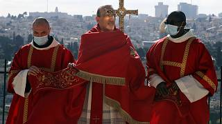 Latin Patriarch of Jerusalem Pierbattista Pizzaballa, center, holds a cross on Palm Sunday on the Mount of Olives in Jerusalem, March 28, 2021.