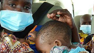 Uma mulher com uma criança ao colo é levada de avião de Palma para Pemba, em Moçambique