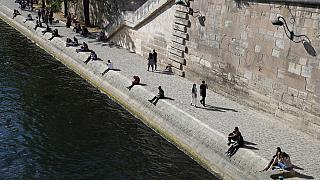 FILE: Parisians sit in the sun along Seine river banks in Paris, May 23, 2020