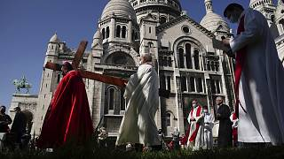 Archbishop Michel Aupetit, left, carries the holy cross at the Way of the Cross ceremony as part of the Holy Easter celebration, in the Sacre Coeur basilica, in Paris, France.