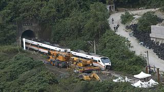 Rescue workers remove a part of the derailed train near Taroko Gorge in Hualien, Taiwan on Saturday, April 3, 2021.