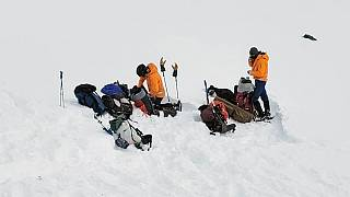 Volunteers work near the scene of a helicopter crash close to the Knik Glacier in Alaska on Sunday, March 28, 2021.