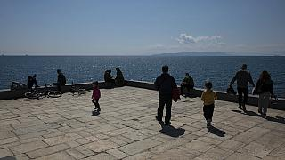 People enjoy a sunny day at a square at Piraeus port town near Athens