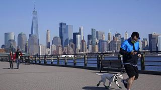 people enjoy the warming weather and a view of lower Manhattan at Liberty State Park in Jersey City