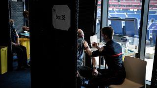 Los ciudadanos reciben una dosis de la vacuna COVID en un centro de vacunación masiva instalado en el estadio de fútbol del Olímpico de Lyon, el sábado 3 de abril de 2021.