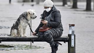 A woman with a face mask and a dog sit on a bench at the almost abandoned downtown in Duisburg, Germany, Monday, Jan. 25, 2021.