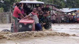 جنود أندونيسيين يستخدمون جراراً لمساعدة السكان على عبور طريق غمرته مياه الفيضانات في مالاكا تينجا بمقاطعة نوسا تينجارا الشرقية