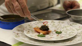 Архивное фото. Шеф-повар украшает блюдо с черной икрой.
