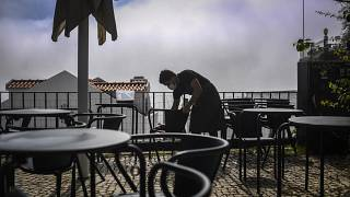 A waiter cleans chairs at the Portas do Sol viewpoint in Lisbon as the Portuguese government eased coronavirus restrictions.