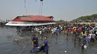 Divers carry a dead body after recovering from the capsized boat in Shitalakshya River, in Narayanganj.