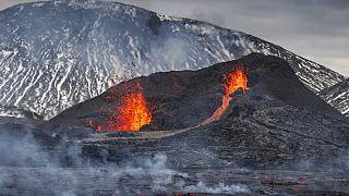Steam and lava spurt from a new fissure on a volcano on the Reykjanes Peninsula in southwestern Iceland, Monday, April 5, 2021.